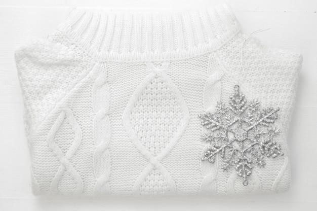 Maglione bianco di inverno tricottato e decorazione del fiocco di neve su fondo di legno bianco