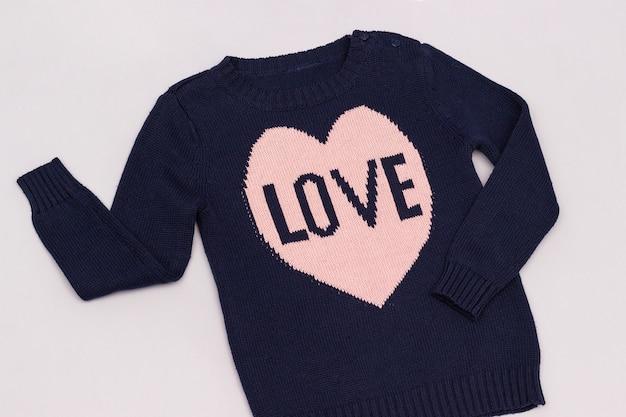 Maglione blu femmina con cuore rosa modello e scritta love. concetto dei vestiti di sguardo di modo della donna