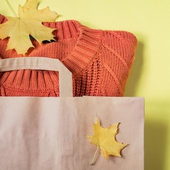 Maglione caldo della donna arancio in pacchetto del mestiere di carta su giallo