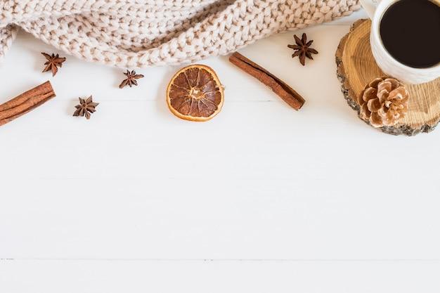 Maglione ed elementi di natale, una tazza di caffè su un fondo di legno bianco