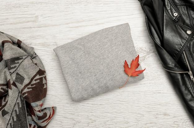 Maglione grigio con spazio per il testo, una giacca nera, sciarpa e foglie d'autunno