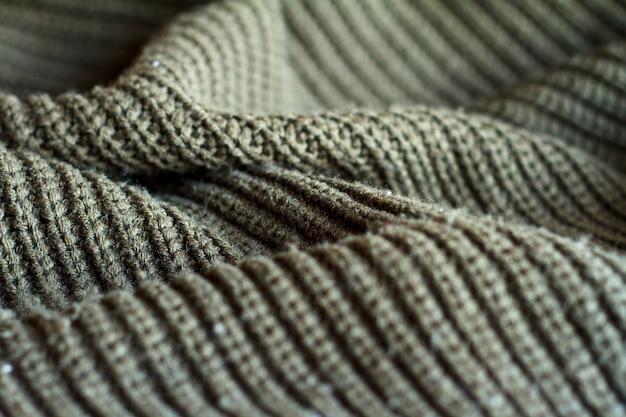 Maglione lavorato a maglia color oliva di primo piano fatto di trama di lana naturale