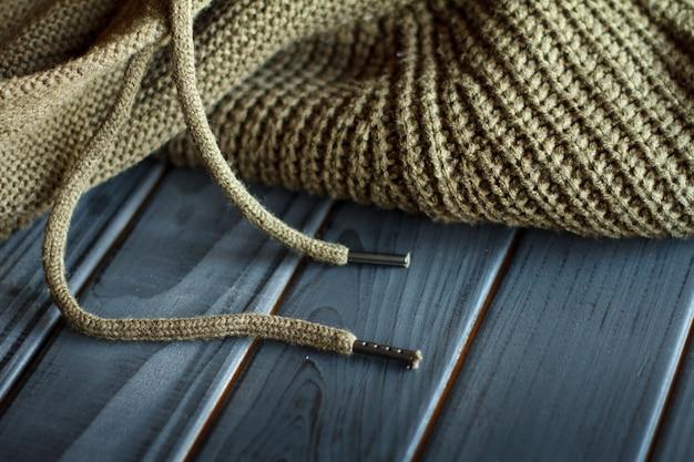 Maglione lavorato a maglia color oliva in lana naturale su una superficie di legno nera