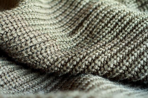 Maglione lavorato a maglia color oliva in primo piano realizzato con trama di lana naturale, pieghe ondulate,