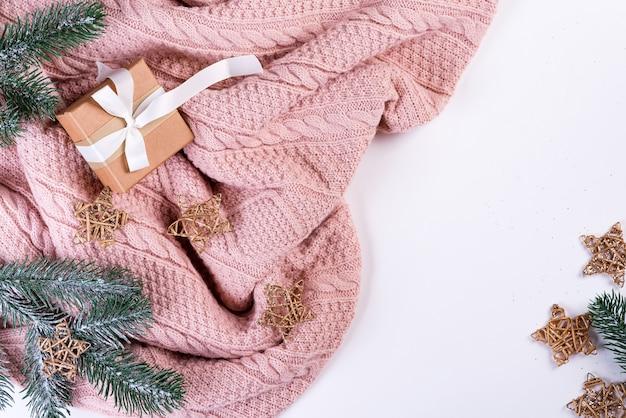 Maglione lavorato a maglia rosa con confezione regalo, decorazioni natalizie e rami di abete, vista dall'alto. natale ancora in vita