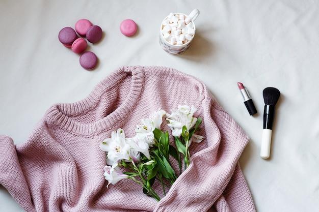 Maglione lavorato a maglia rosa, prodotti cosmetici e fiori bianchi