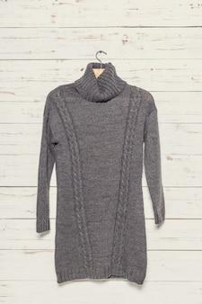 Maglione lavorato a maglia su stendibiancheria in superficie di legno