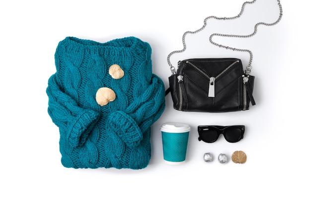 Maglione turchese, borsa, occhiali da sole, foglie secche e caffè in vista dall'alto.