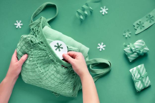 Maglione verde menta impacchettato in borsa a rete o a rete. zero rifiuti regali di natale.