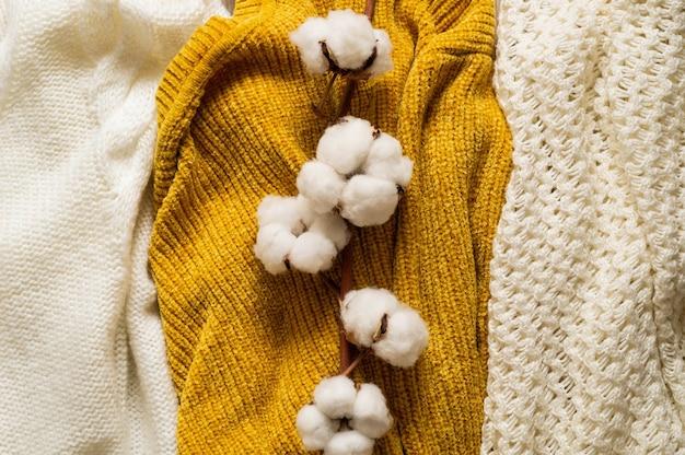 Maglioni caldi. pila di vestiti a maglia con foglie di autunno, concetto di autunno inverno.