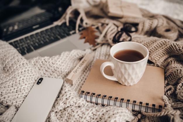 Maglioni e tazza di tè con notebook, laptop e telefono