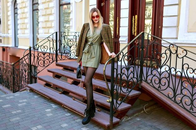 Magnifica donna bionda alla moda in posa sullo stretto vicino a hotel di lusso in stile classico, atmosfera europea, abbigliamento moderno alla moda, blogger in posa per strada.