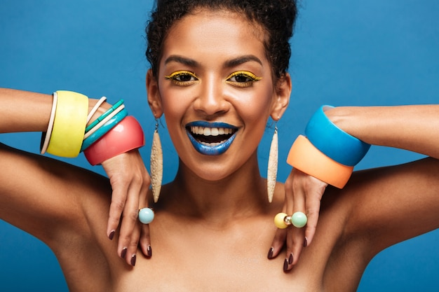 Magnifica donna seminuda con trucco colorato che sorride e che dimostra gli accessori sulle sue braccia, isolate sopra l'azzurro