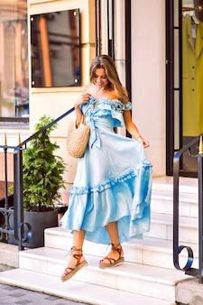 Magnifica giovane donna alla moda positiva in posa per strada, indossa un abito alla moda femminile e una borsa di paglia, colori tenui e solari, periodo delle vacanze estive.