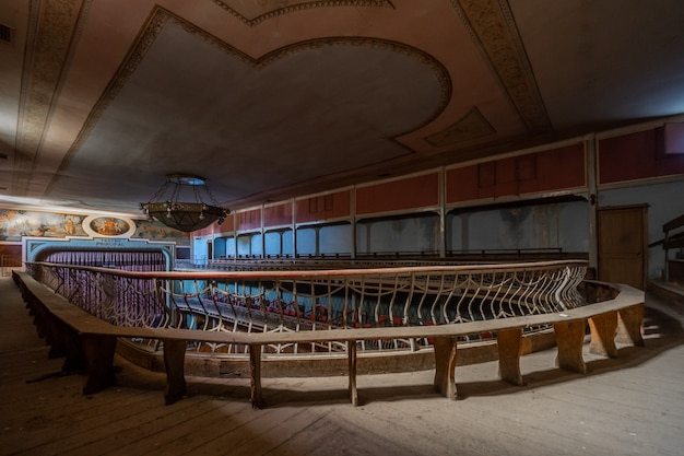 Magnifico teatro classico abbandonato con murales sul soffitto e lampada spettacolare