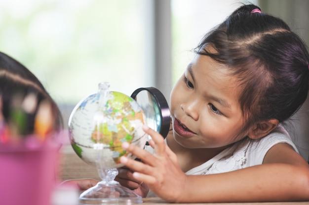 Magnifier asiatico sveglio di uso della ragazza del bambino da osservare e studiare al globo in aula