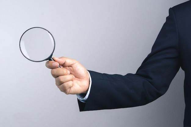 Magnifier della holding della mano dell'uomo di affari per ispezione