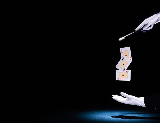 Mago che esegue il trucco della carta da gioco con la bacchetta magica contro fondo nero