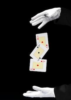 Mago che esegue il trucco della carta da gioco contro fondo nero