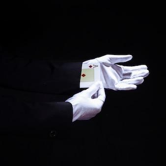 Mago che rimuove la carta da gioco degli assi dalla mano contro fondo nero