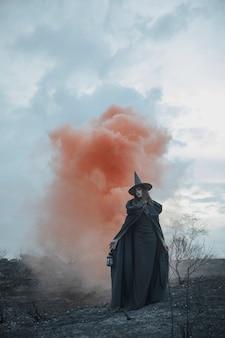 Mago maschio in abiti neri con nebbia rossa