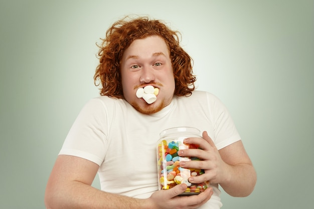 Mai abbastanza. primo colpo di divertente giovane uomo grassoccio con i capelli ricci di zenzero tenendo stretto barattolo di caramelle, guardando con espressione sorpresa sorpreso, la bocca piena di marshmallow