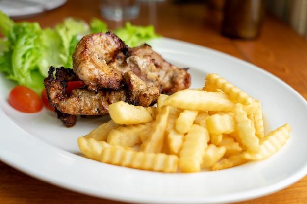 Maiale alla griglia e patatine fritte, disposte su un bel piatto di cibo bianco con insalata