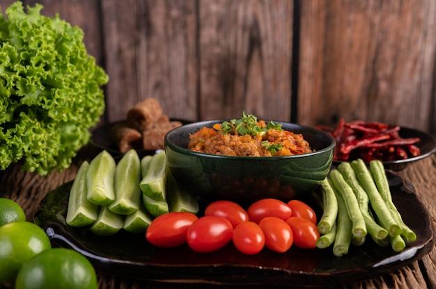Maiale dolce in una ciotola nera, completo di cetrioli, fagioli lunghi, pomodori e contorni
