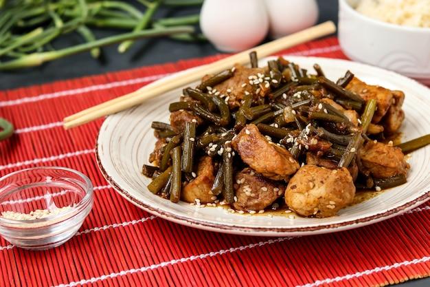Maiale fritto con frecce di aglio e salsa di soia, cosparso di semi di sesamo in un piatto