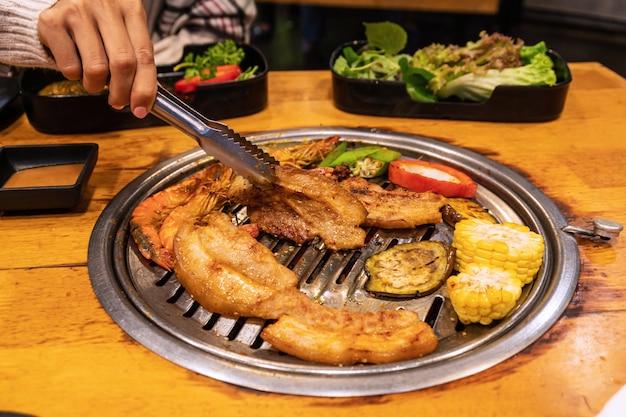 Maiale, gamberi e verdure vistosi sulla griglia a carbone per barbecue yakiniku in stile coreano o giapponese.