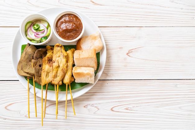 Maiale satay con salsa di arachidi e sottaceti che sono fette di cetriolo e cipolle in aceto