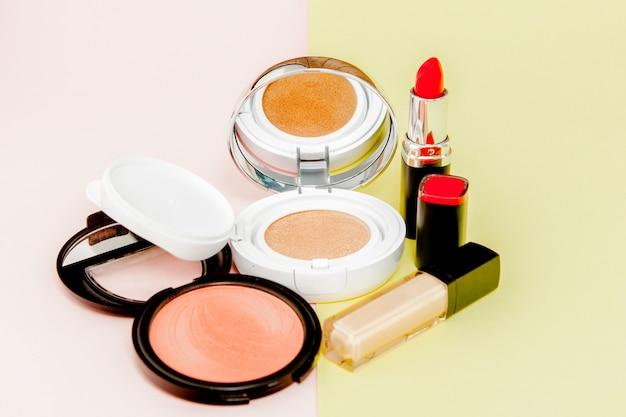 Make up prodotti che si rovesciano su uno sfondo giallo e rosa brillante con spazio di copia