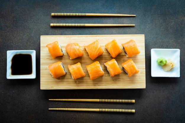 Maki del rotolo di sushi della carne di pesce del salmone sul piatto di legno