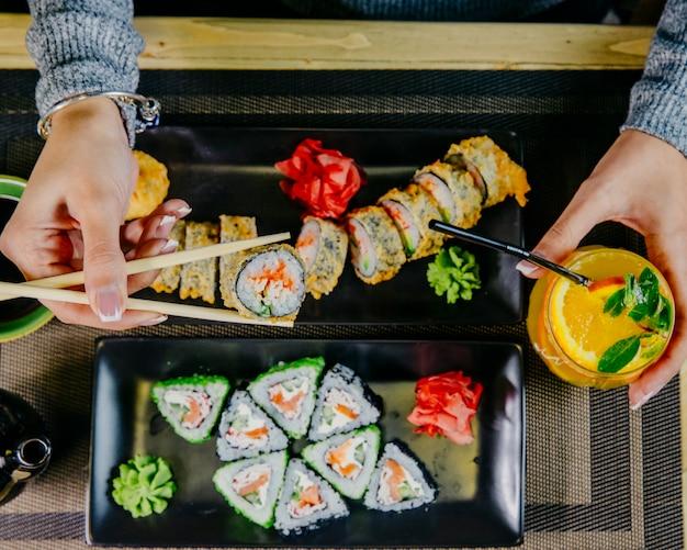 Maki mangiatore di uomini di sushi unagi con la vista superiore del cocktail arancio