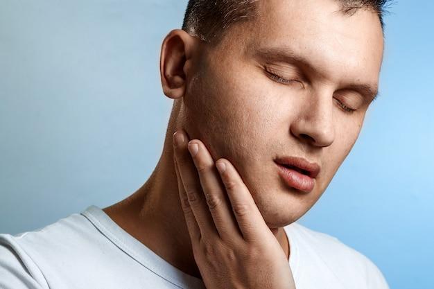 Mal di denti. ritratto di un primo piano di uomo sul blu