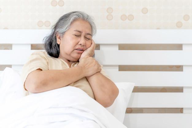 Mal di denti senior asiatico dei pazienti della donna fa male - concetto medico e di sanità dei pazienti anziani