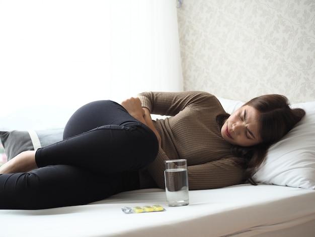 Mal di stomaco della donna e posa sul letto.