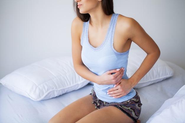 Mal di stomaco. giovane donna malsana con mal di stomaco che si appoggia sul letto a casa