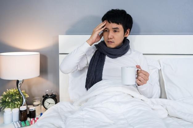 Mal di testa uomo malato e bere una tazza di acqua calda sul letto