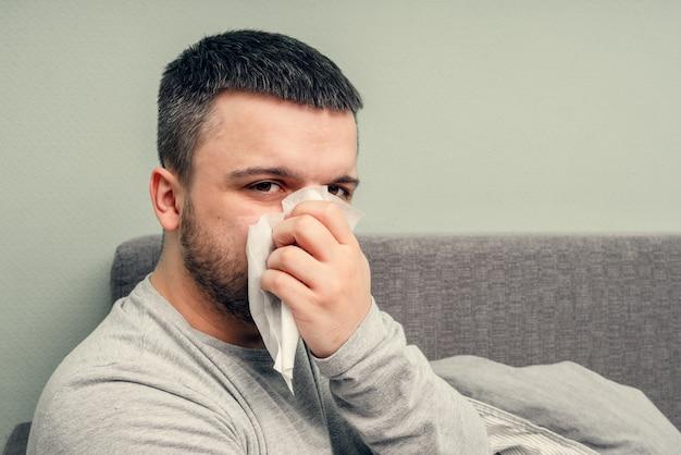 Malattia. esultare a casa. un giovane è malato, viene curato a casa. soffia il naso in un tovagliolo, naso che cola. infezione, epidemia, portatore di bacillo.