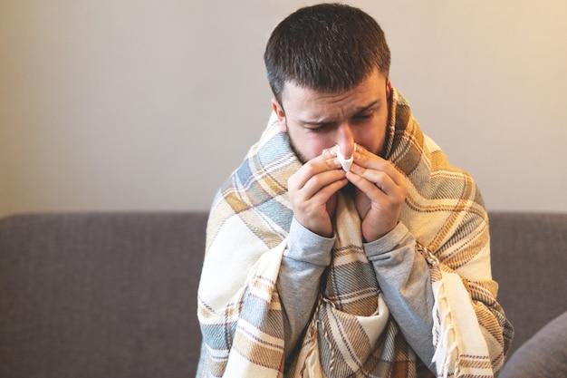 Malattia. esultare a casa. un giovane è malato, viene curato a casa. soffia il naso in un tovagliolo, naso che cola. infezione, epidemia, portatore di bacillo