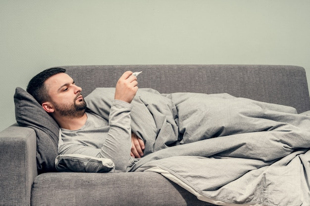 Malattia. esultare a casa. un giovane è malato, viene curato a casa. soffia il naso in un tovagliolo, naso che cola. misurazione della temperatura corporea. infezione, epidemia, portatore di bacillo. coronavirus