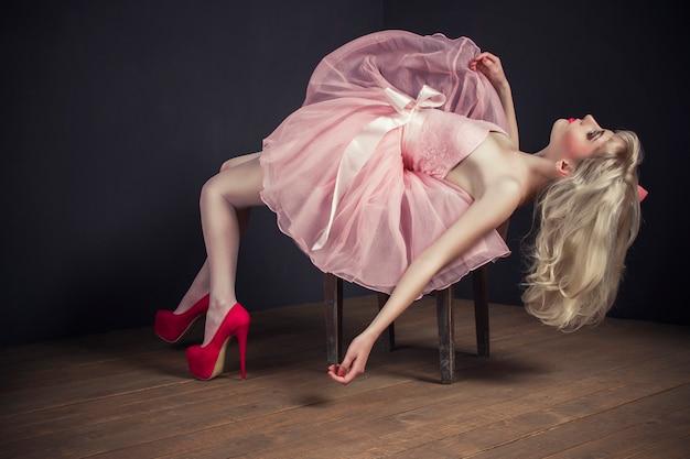 Malvina ragazza in abito rosa sdraiato sulla sedia, moda