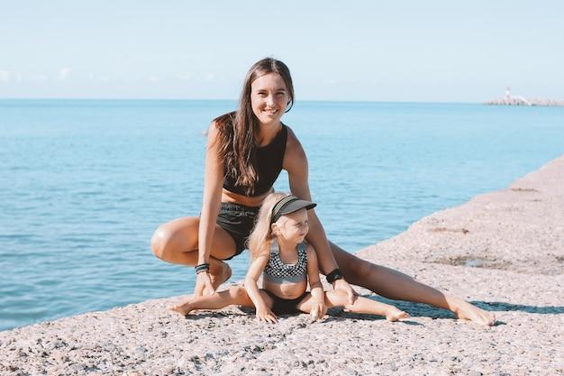 Mamma adatta della donna dei giovani con la piccola ragazza sveglia che si esercita insieme sulla spiaggia di mattina, stile di vita sano, famiglia di sport
