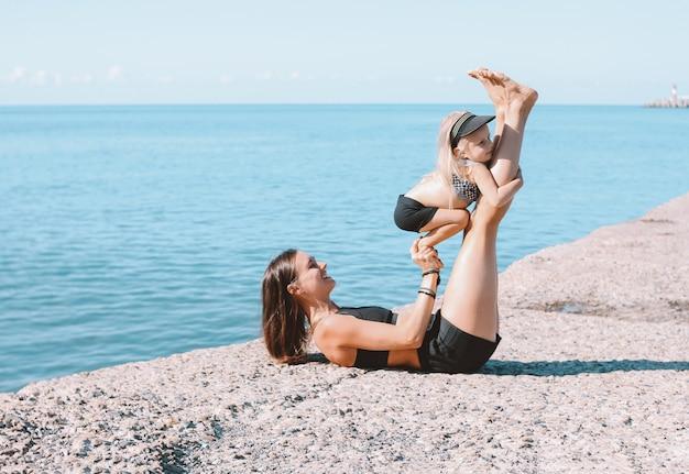 Mamma adatta della donna dei giovani con la piccola ragazza sveglia che si esercita insieme sulla spiaggia di mattina