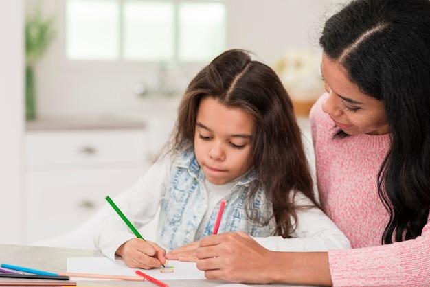 Mamma aiutando la ragazza a colorare il libro