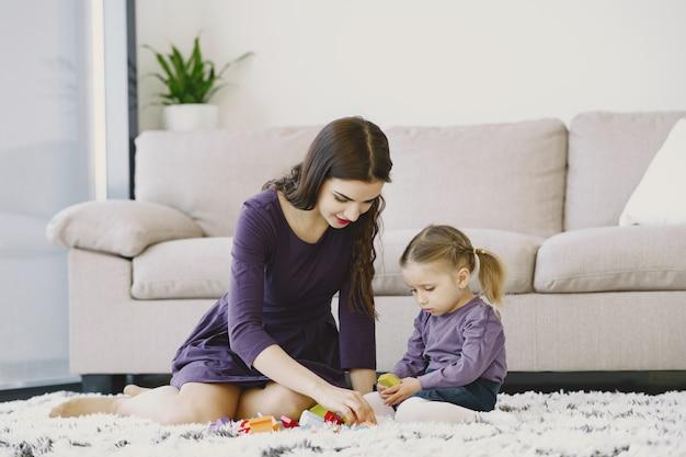 Mamma allegra che gioca ridendo con la figlia del bambino