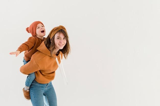 Mamma allegra che offre un giro sulle spalle al figlio