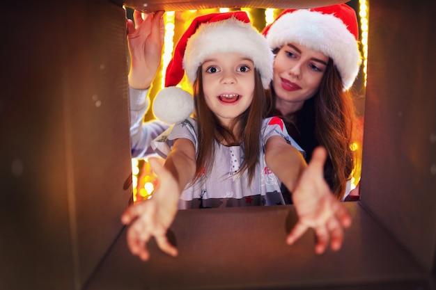 Mamma allegra e la sua ragazza carina figlia aprendo un regalo di natale