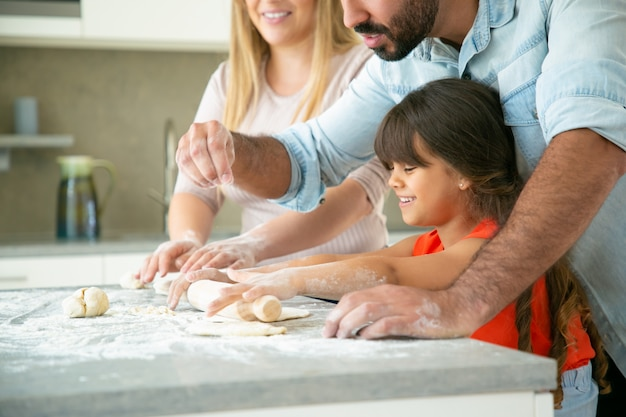 Mamma allegra e papà che insegnano alla figlia felice a rotolare la pasta sul tavolo della cucina con farina disordinata. giovani coppie e la loro ragazza che cuociono insieme i panini o le torte. concetto di cucina familiare